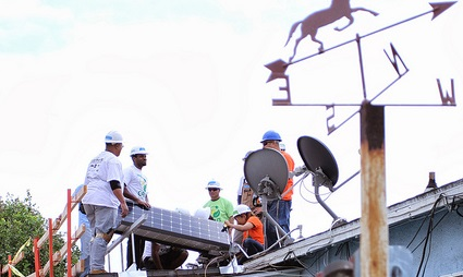 People working together around a half-finished rooftop solar installation are shot from the ground and behind a fence