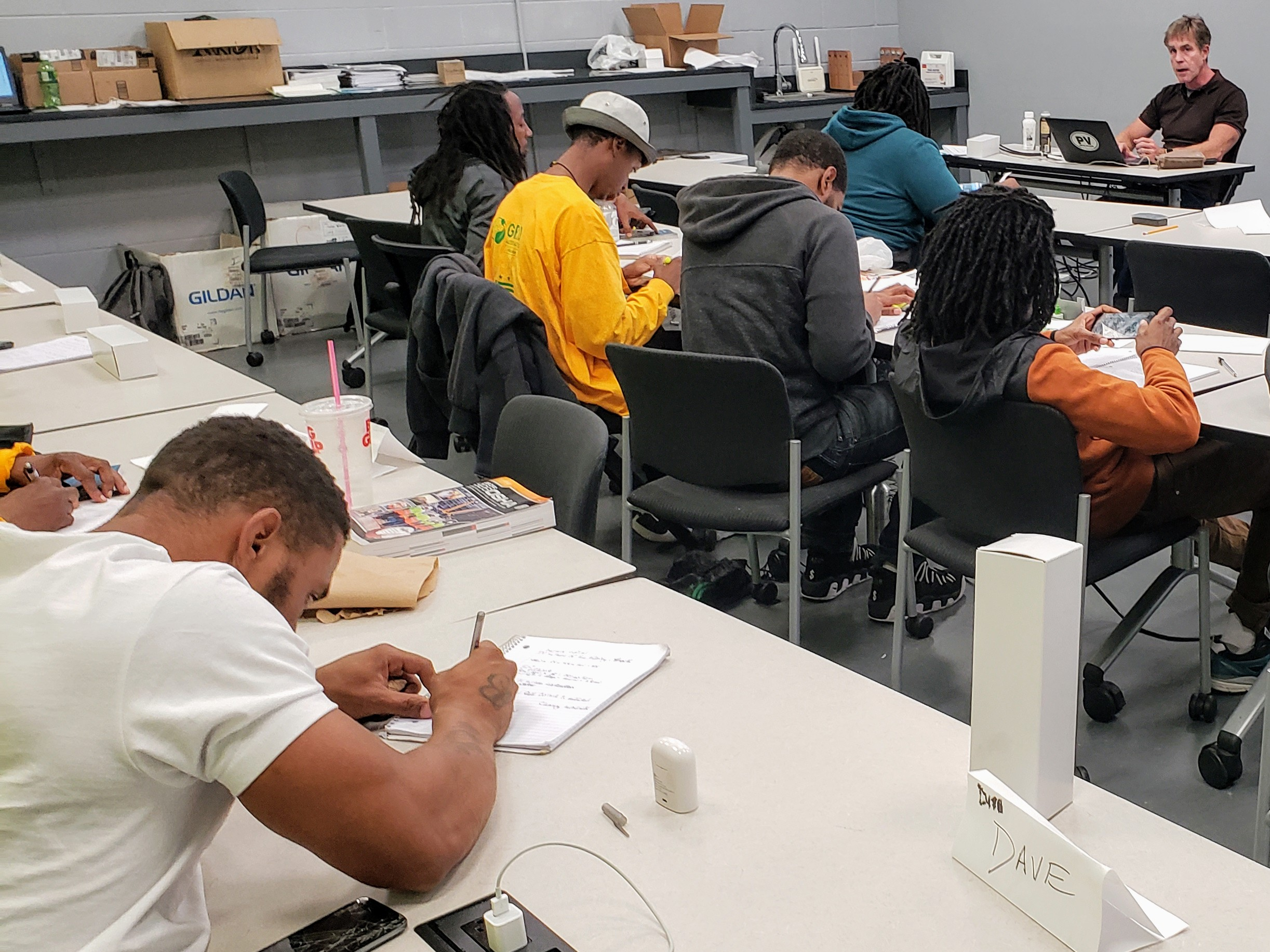 Solar Works DC trainees take notes as solar installation expert Sean White goes through a practice NABCEP exam.