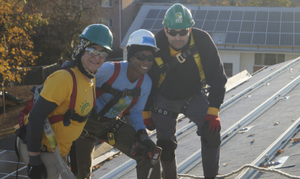 Three people on roof posing with solar array in background holding tools.