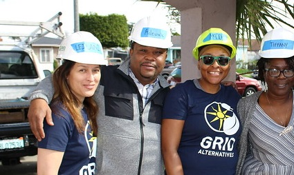 A smiling person, Leilani Sinclair, stands at the end of a row of team members on a GRID Alternatives project