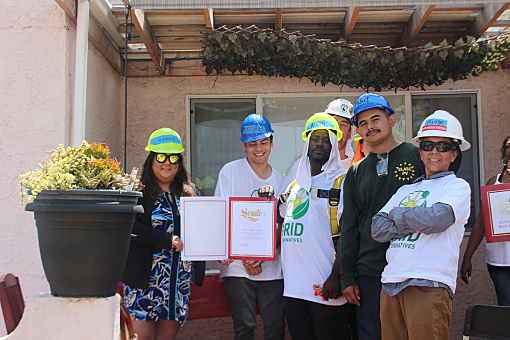 A group of students and instructors poses in front of a house, filled with pride at receiving a certificate