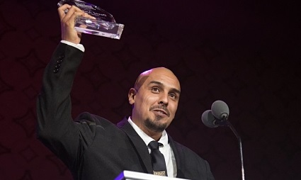An individual with a shave head, wearing a dark suit, holds up an award to celebrate what he is speaking about