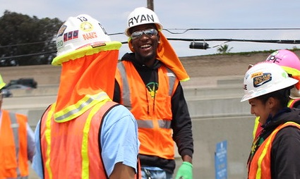 A laughing person in a construction outfit is surrounded by laughing colleagues