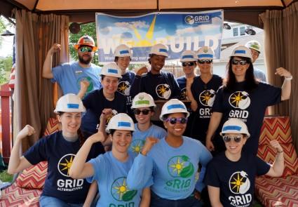 We Build volunteers pose in front of a We Build banner