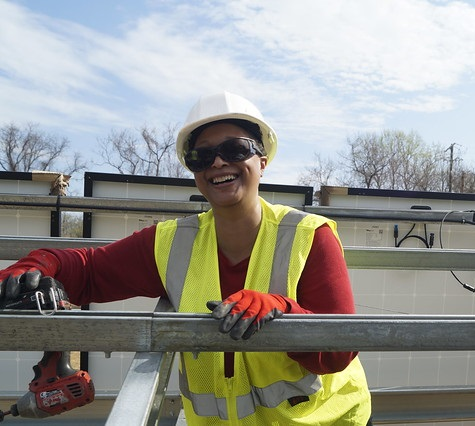 GRID Mid-Atlantic Executive Assistant, Dawn Fong, working at a staff build, leaning on a beam and smiling for the picture.