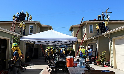 A group of houses receive solar from a team of people, some in yellow Southern California Edison shirts
