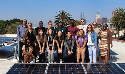 A group poses for a photo on a flat roof covered by solar panels
