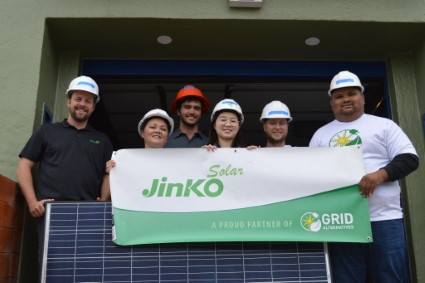 Five Jinko employees pose behind a Jinko sponsorship banner