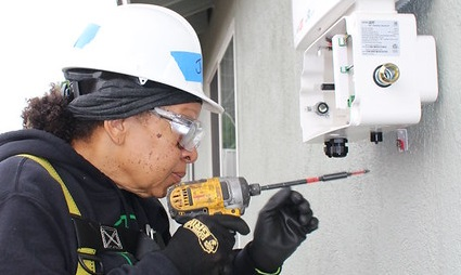 A person with a drill demonstrates extreme concentration and precision inserting a screw in drywall