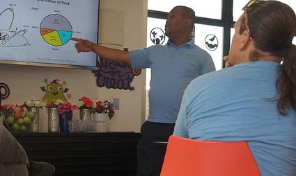 A GRID Alternatives staff members uses pie chart slides to explain solar