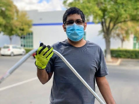 Alexis is wearing glasses, a facemask, a grey t-shirt and jeans. He is holding a piece of bent metal with yellow work gloves on.