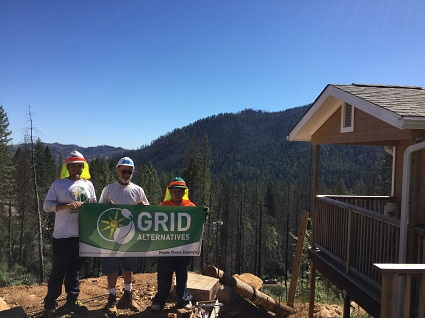 Image: Homeowner, GRID staff, and volunteers in front of the Wasik home with forest in the background.
