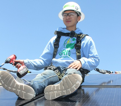 Tony Nguyen siting on a solar panel.