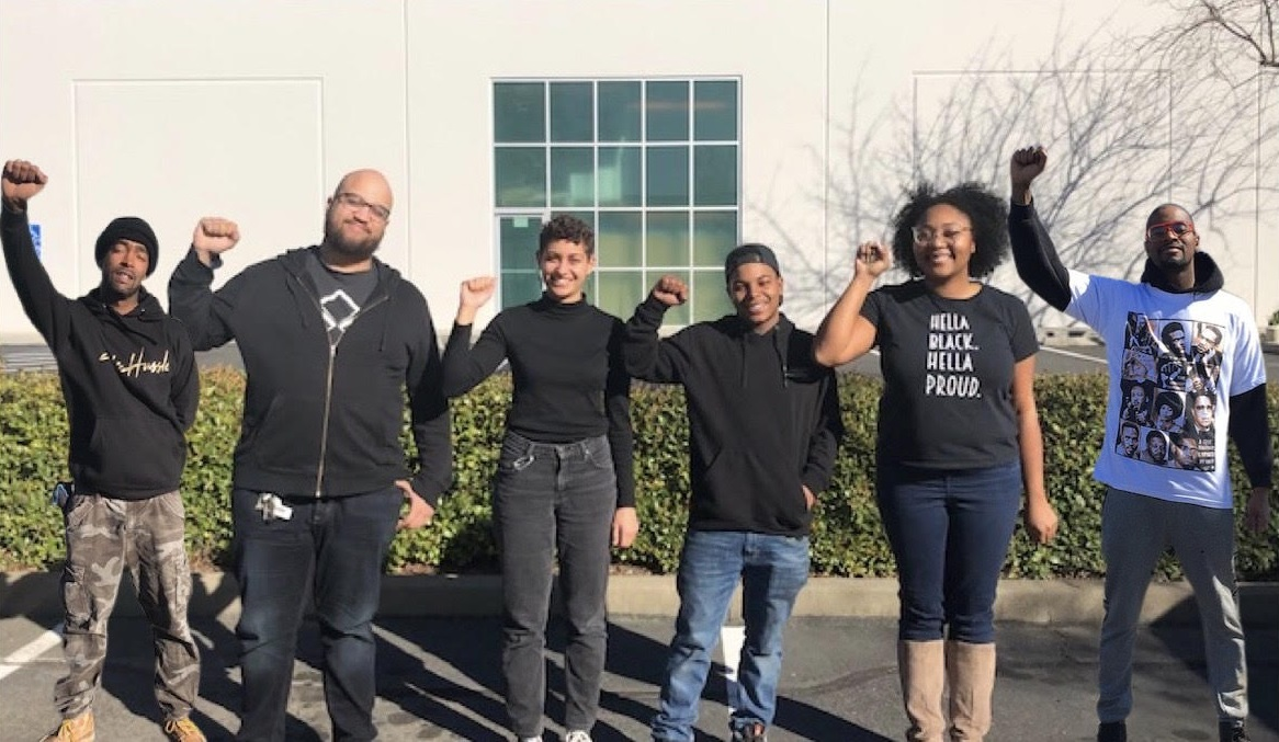 black employees with their fist up