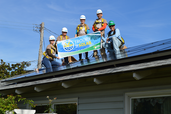GRID Veterans Liason Jennifer Watkins (far left), alongside three US military veteran volunteers and GRID Solar Installation Supervisor Andrew Hayes hold a GRID Alternatives Troops to Solar banner with the solar panel system they just