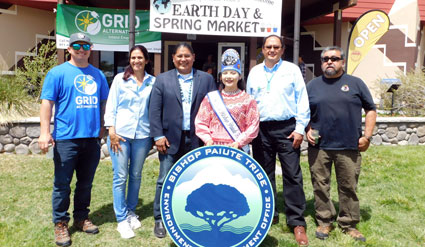 Representatives from GRID, the Bishop Pauite Tribe, and the DOE pose behind the Bishop Paiute tribal seal.
