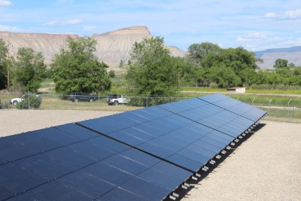 A view of solar arrays with mountains in the background