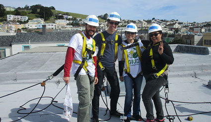 Four volunteers from the CPUC pose on a rooftop where they're installing solar.