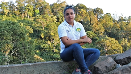 Carmen sits on a stone wall with Nicaraguan landscape in the background