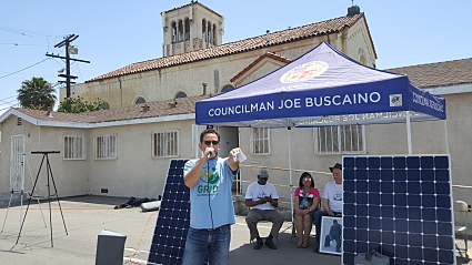 In an outdoor setting, a leader in a blue GRID Alternatives shirt makes an announcement on a microphone