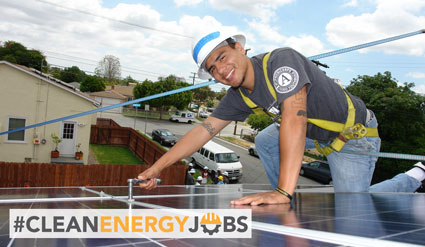 A job trainee installs solar on a roof.