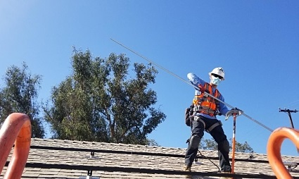 A GRID Alternatives installation worker bends conduit on the roof