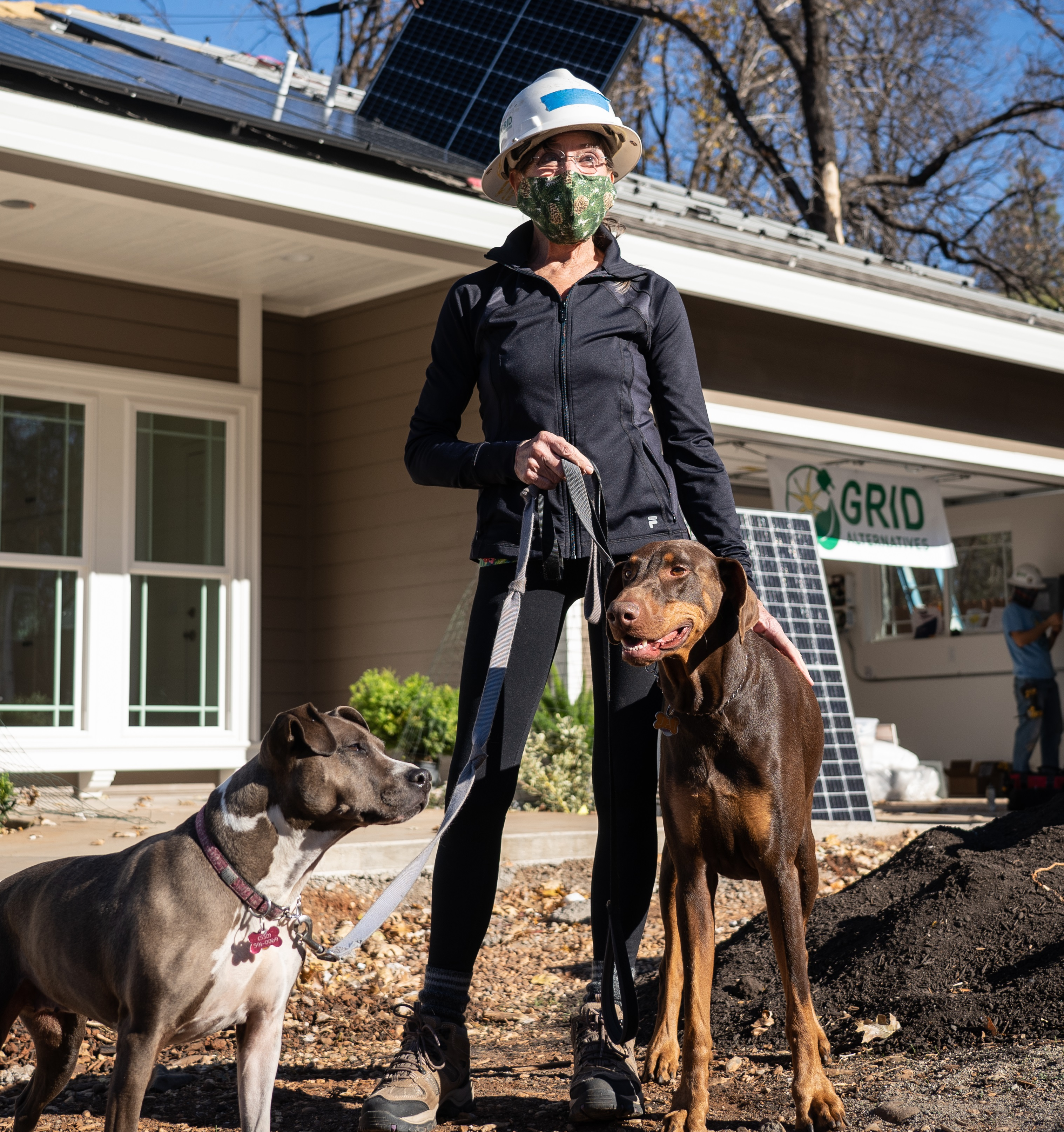 Lynn stands in front of her almost completed new Paradise home wearing PPE with 2 of her dogs. Behind her, solar panels and a GRID banner are visible.
