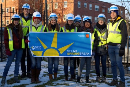 Solar Spring Break students donned in construction gear pose with a SSB banner!