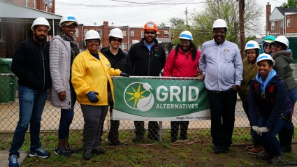 NAACP volunteers, GRID staff, and homeowner Wade Watkins gather by a GRID banner