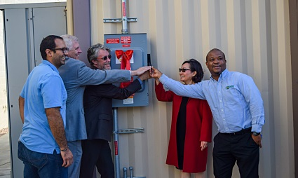 Three people stand to the left of a breaker box and two people stand to the right of it, with everyone getting ready to flip the switch