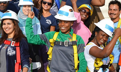 Diverse individuals, ready for construction, hold up their arms and cheer in celebration