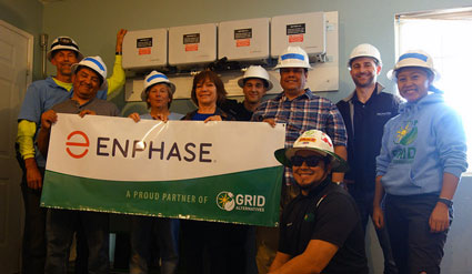 Homeowner Ofelia Eguia poses with GRID staff and volunteers in front of her brand new solar plus storage system.