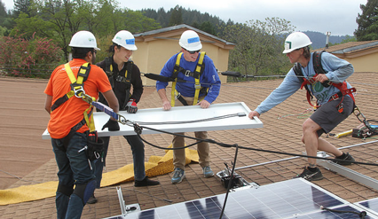 Participants install a solar panel on the Little Lake Grange rooftop.