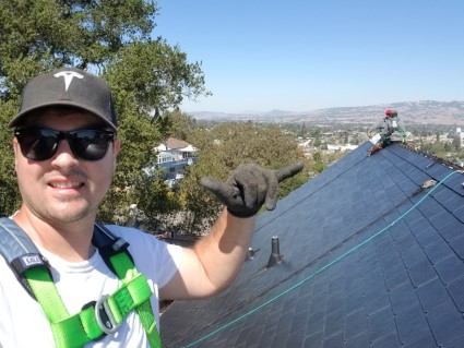 Evan, a previous GRID volunteer, poses in a Tesla hat on top of a roof.