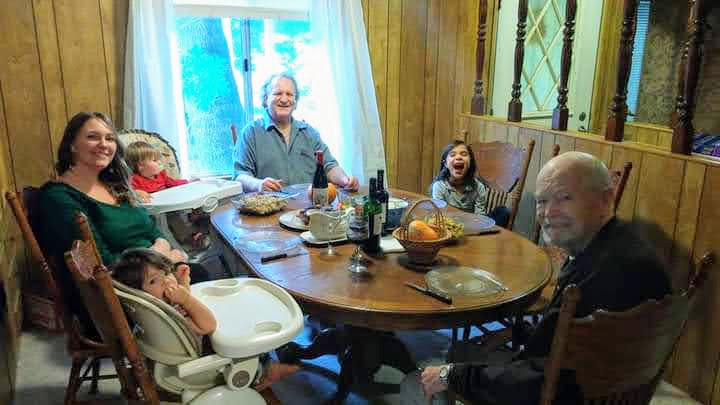 Kristen and her three children, father, and grandfather sit around the dining table.