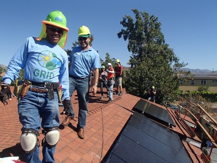 GRID staff in hard hats smile next to a newly installed rooftop solar array.