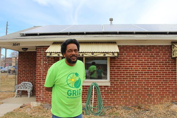 Gary stands proudly in front of his home and GRID-installed solar panels, in Denver, wearing his green GRID t-shirt