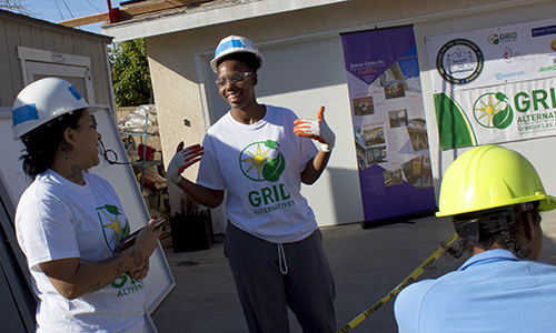 Two trainees laugh on a GRID Alternatives jobsite during a special install in partnership with the NAACP.