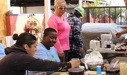 A diverse GRID Alternatives team enjoys a meal around a patio table