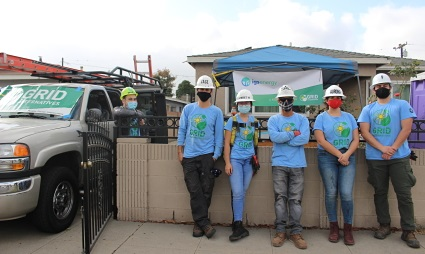 Five GRID Alternatives team members stand out in a row in front of a IGS Energy banner, while another GRID team member leans on a truck with a house in the background