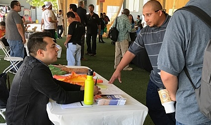 Two people with an interest in the solar industry meet under a tent