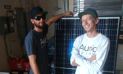 Two men standing in front of solar panel