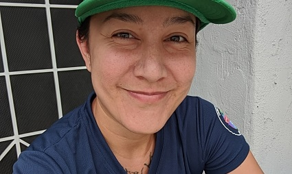 A person with a green cap and a blue shirt with a piece of Pride art faces the camera