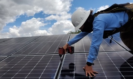 An installer with a black mask worn as face protection uses a drill to secure solar panels