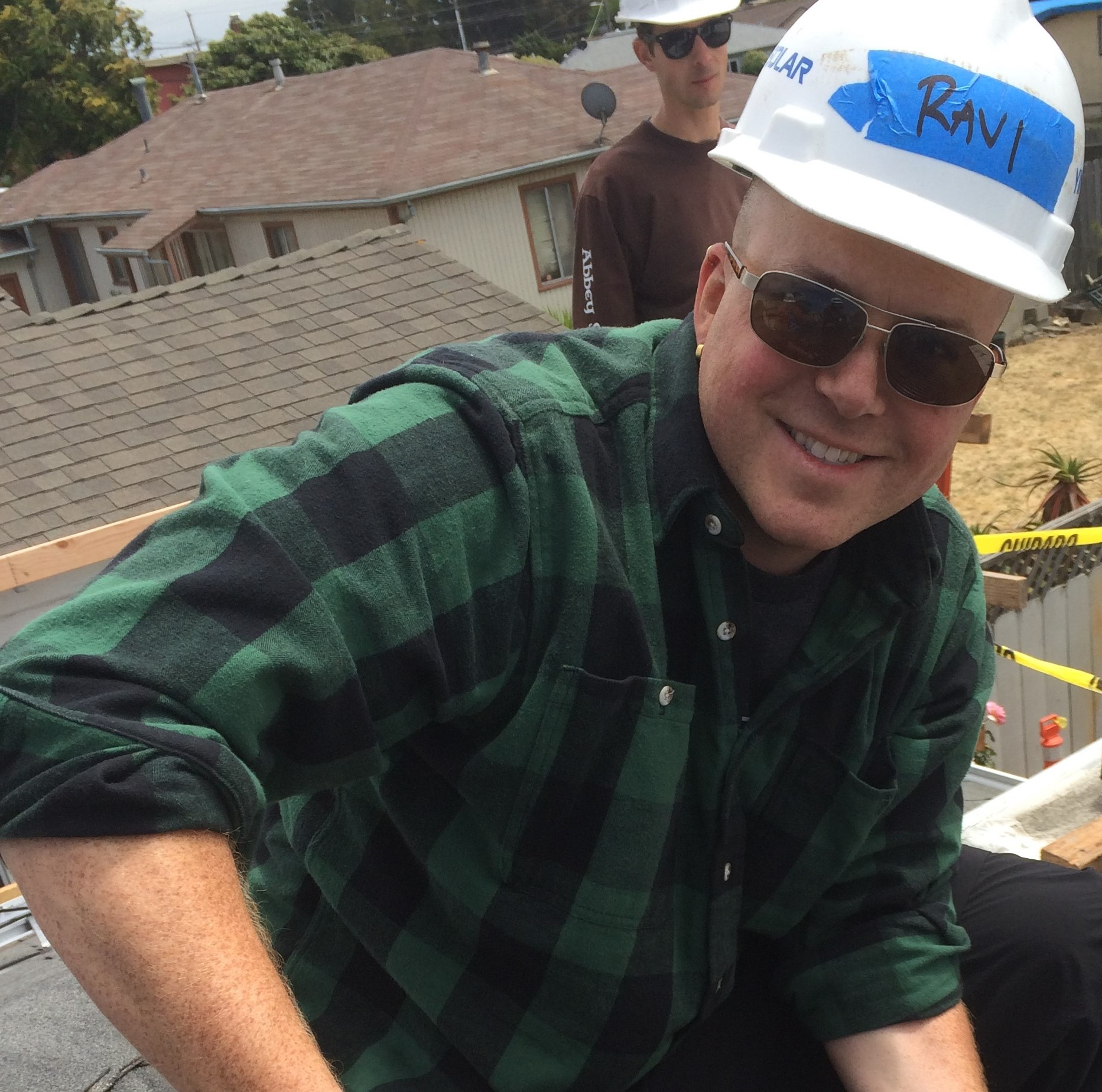 Ravi, in a hard hat, on a roof, smiles at the camera as he holds a drill