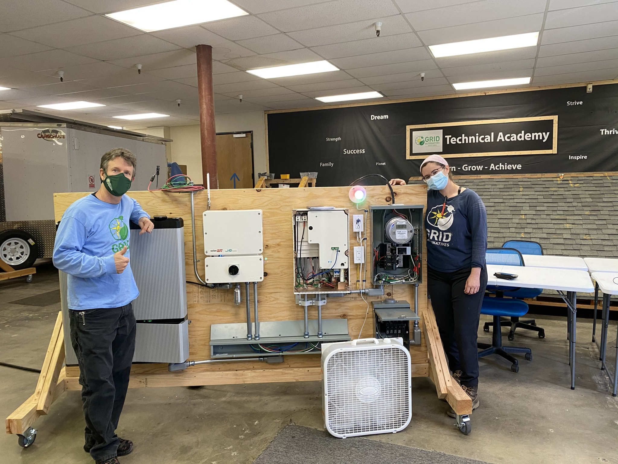 Steve and Monica show off GRID North Valley's new battery storage and EV charger training wall in our Technical Academy.