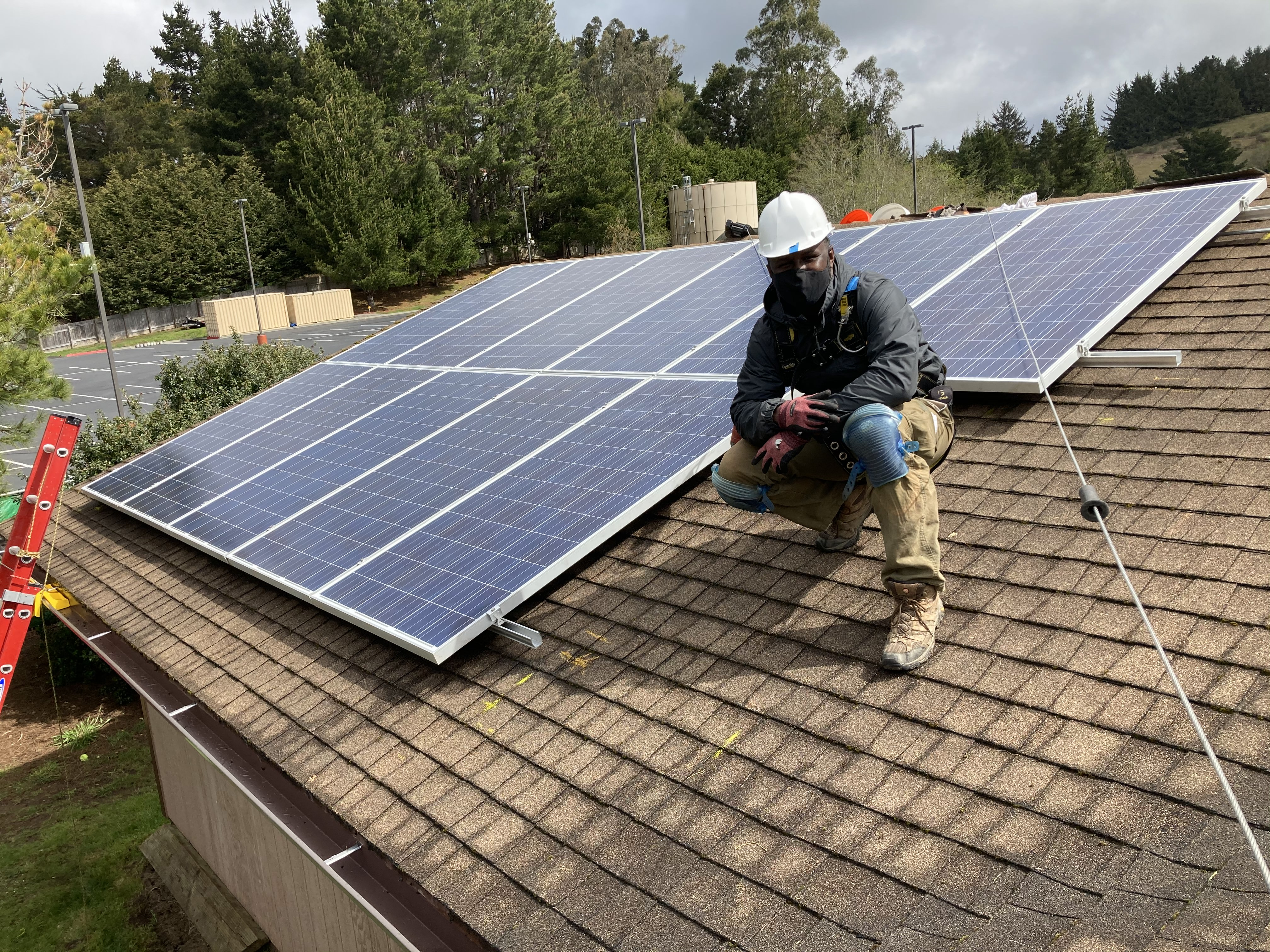 IMG: Garrison Davis poses in front of several solar panels on a roof