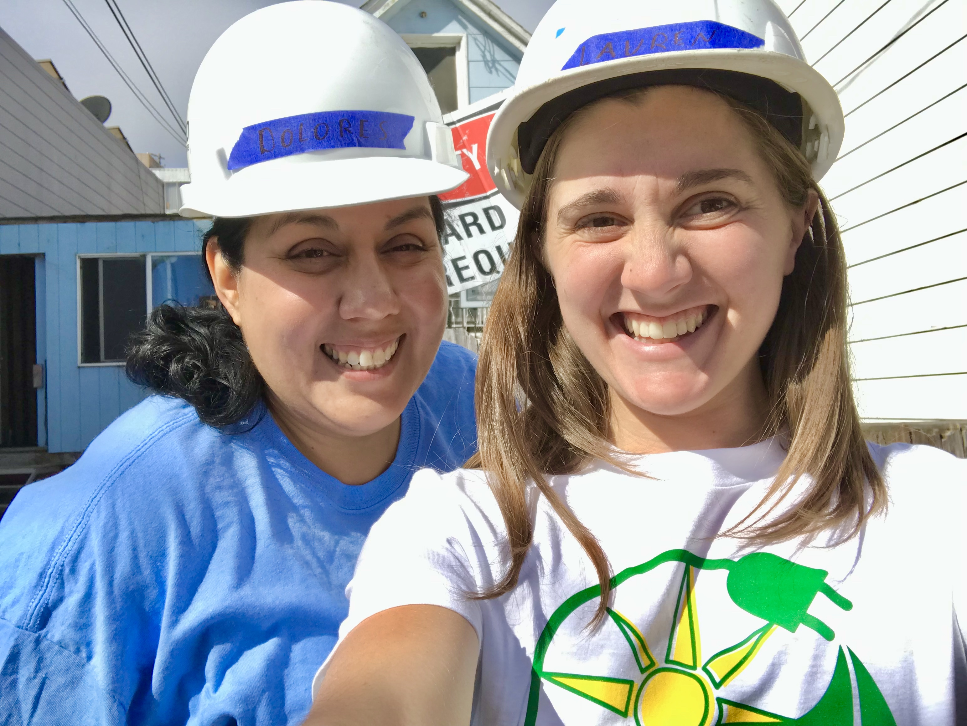 Dolores Garay and Lauren Morgan take a selfie while wearing hard hats at a GRID install