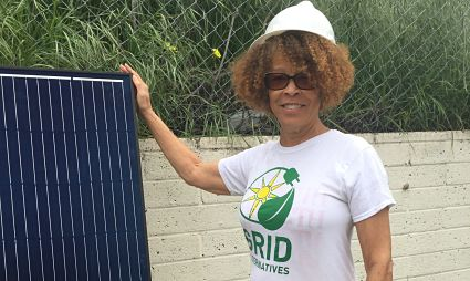 Janice McMurray stands in her garden next to solar panel