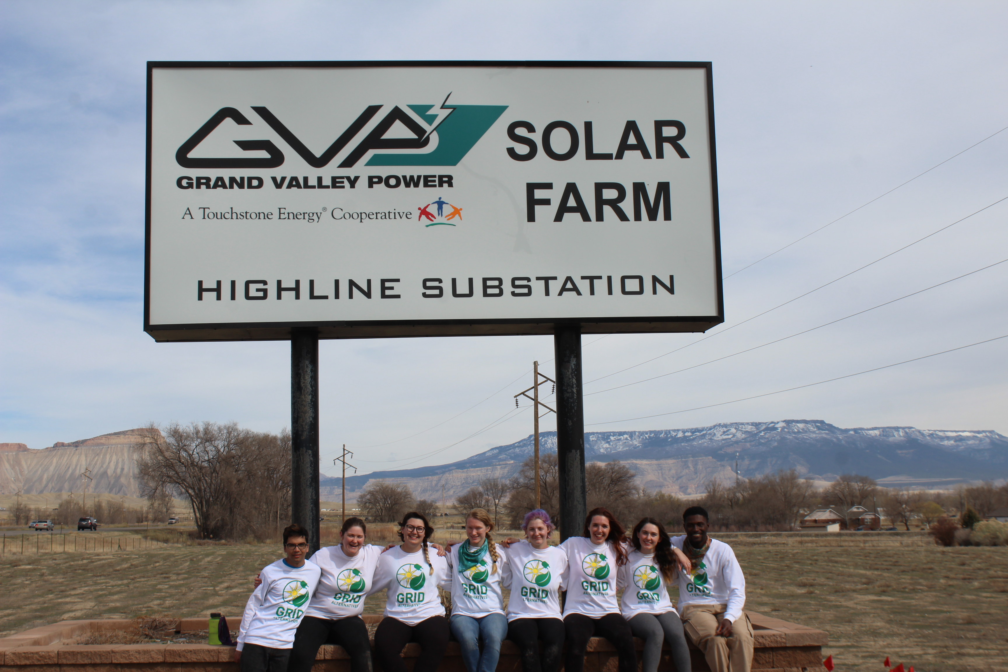 Students standing in front of sign at Grand Valley Power utility community solar farm site